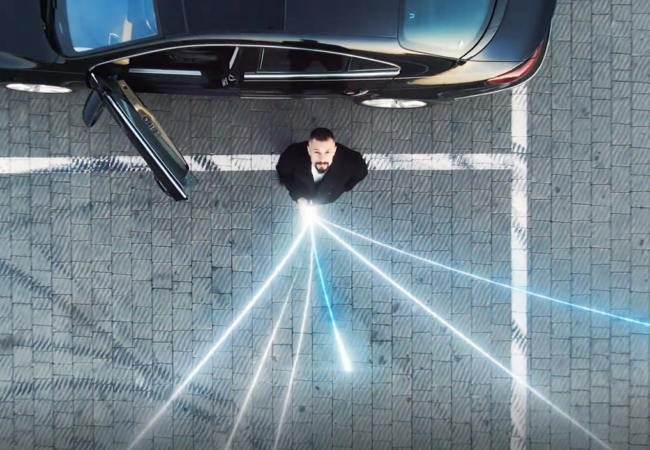Man stood next to a car with data connections shooting from his phone.